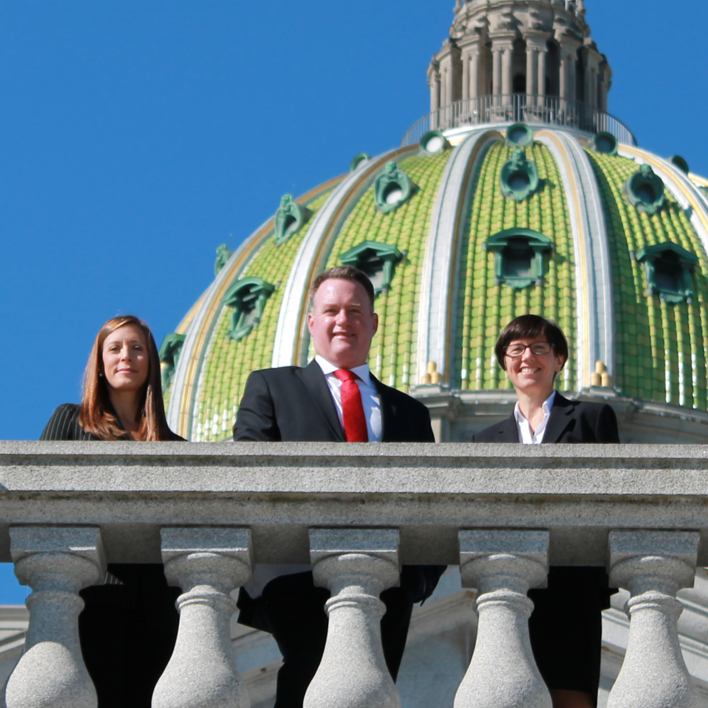 Three people standing in front of state capital building